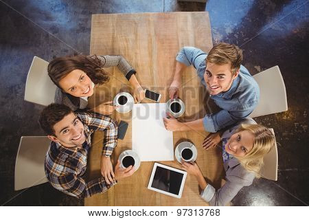 Portrait of smiling friends sitting and drinking coffee at coffee shop