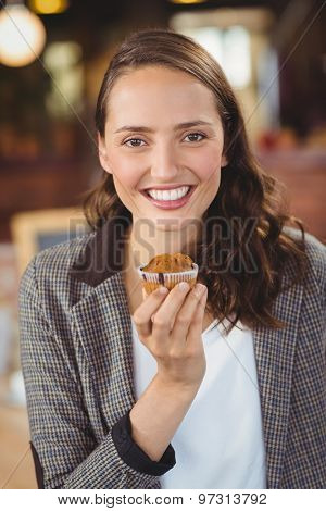 Portrait of smiling young woman showing muffin at coffee shop