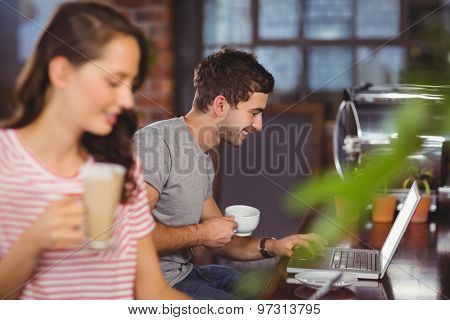 Smiling young man sitting at bar and using laptop at coffee shop