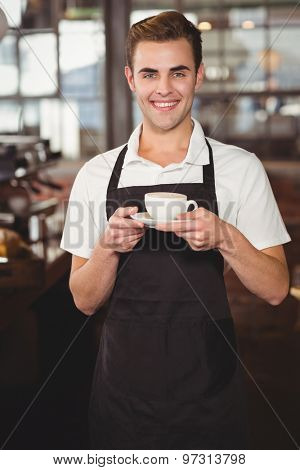 Portrait of smiling barista holding cup of coffee at coffee shop