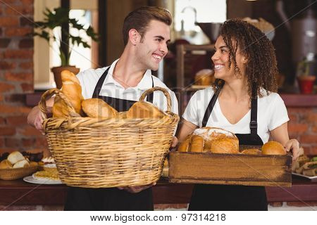 Smiling waiter and waitress holding basket full of bread rolls at coffee shop
