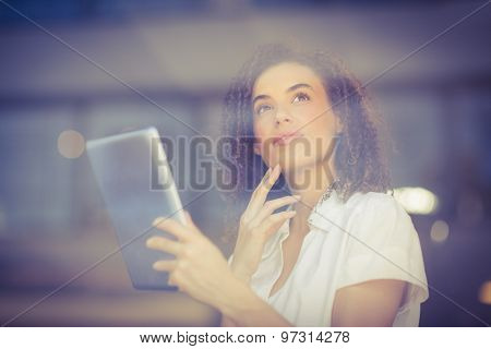 Thoughtful woman using a digital tablet at the coffee shop