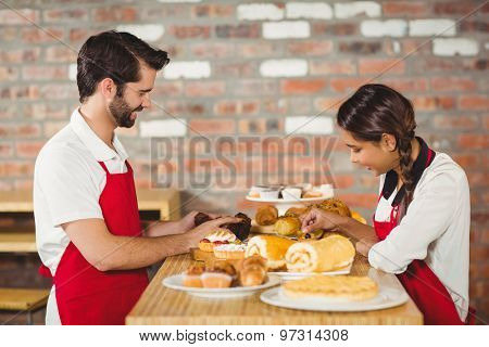 Waiters tidying up pastries on the counter at the coffee shop