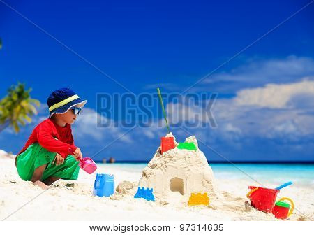 little boy building sandcastle on tropical sand beach