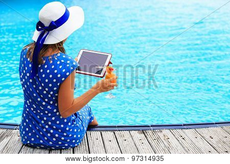 woman with cocktail and touch pad near swimming pool