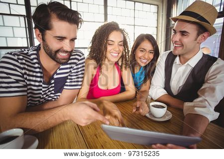 Laughing friends pointing and looking at tablet computer at coffee shop