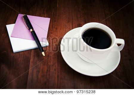Empty white porcelain cup of coffee and pen with notes on brown wooden background