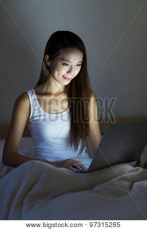 Woman working with laptop computer on bed