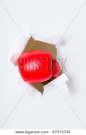 Punching boxing glove though over white paper