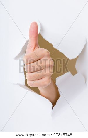 Thumb up hand gesture through a hole in paper