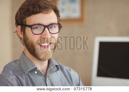 Happy hipster sitting at his desk in his office