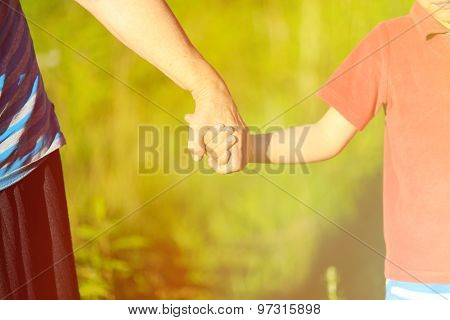 hands of young child and old senior on nature background