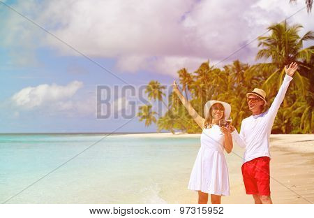 happy loving couple drinking wine at beach