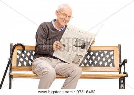 Senior man reading a newspaper seated on a wooden bench isolated on white background