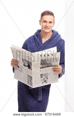 Vertical shot of a cheerful young man in a blue bathrobe holding a newspaper and leaning against a wall isolated on white background