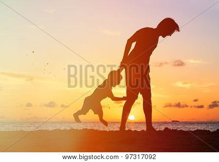 silhouettes of father and son having fun at sunset