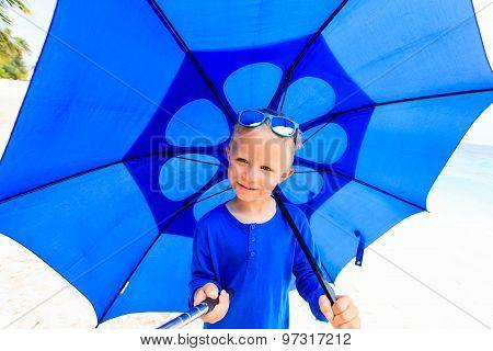 Selfie of happy little boy with umbrella on rainy day
