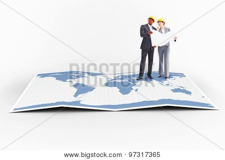 Business people wearing hard hats are discussing against world map
