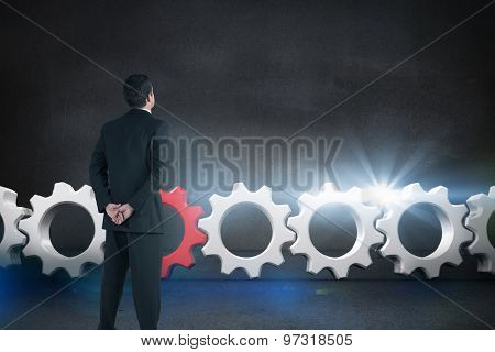 Businessman standing and looking against black wall