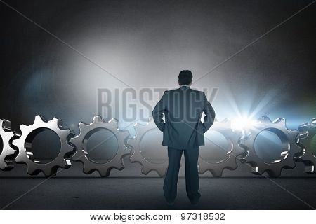 Businessman standing back to the camera with hands on hip against black wall