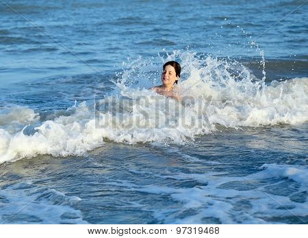Child Splashing In The Waves Of The Sea In Summer