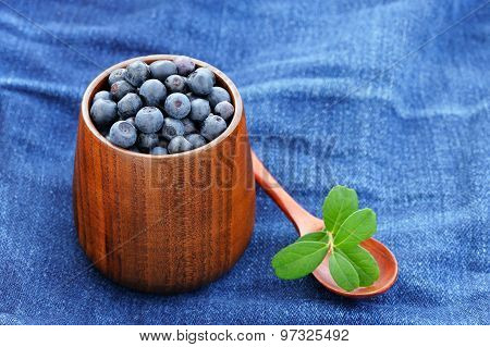 Fresh Wild Blueberries With Green Leaves In Wooden Vase And Wooden Spoon On Indigo Jeans