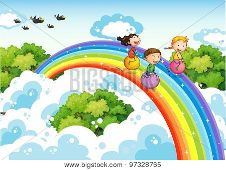 Children bouncing ball over the rainbow