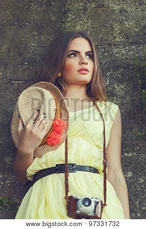 Attractive Young Woman In Yellow Dress Posing Against Old Wall