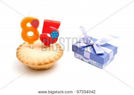 Cupcake With Eighty Five Years Birthday Candle And Gift On White