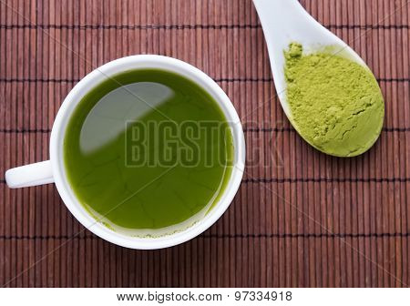 Matcha Tea In A White Cup On The Brown Mat