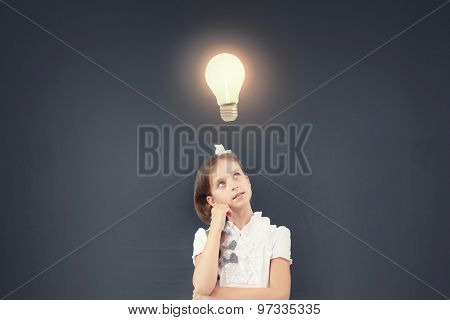 Cute thoughtful girl of school age standing near blackboard