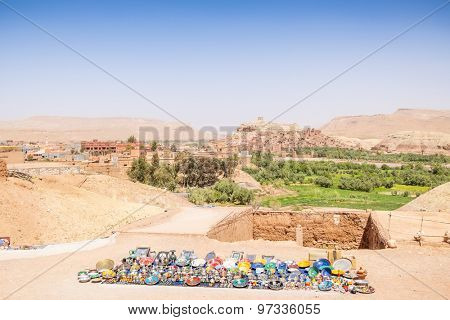 AIT BENHADDOU, MOROCCO - APRIL 10, 2015:  Souvenir stand with clay town of Ait Benhaddou in background