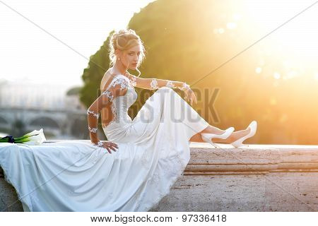 Pretty Bride Sitting On Bridge