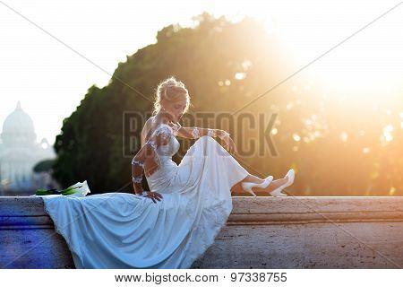 Attractive Bride Sitting On Bridge