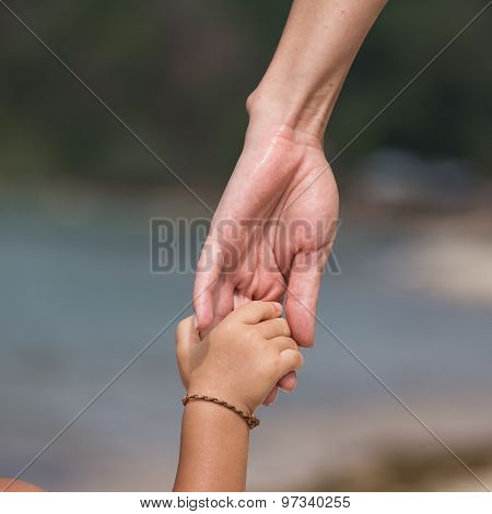 Hands Of Mother And Child On The Beach