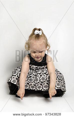 Little Girl In Black And White Dress Sitting