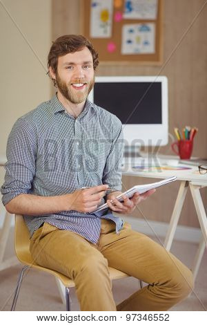Bearded hipster smiling at camera holding notes in his office