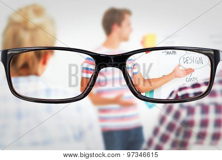 Glasses against smiling young designer presenting ideas to colleagues
