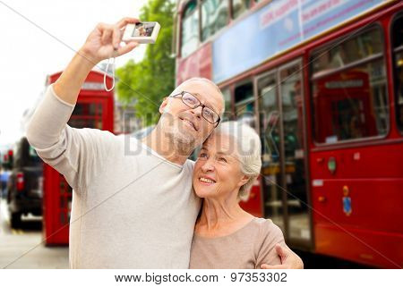 age, tourism, travel, technology and people concept - senior couple with camera taking selfie over london city street background