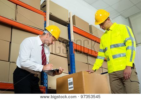 Manager Checking List With Worker In Warehouse