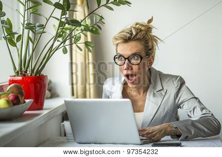 Surprise, shock, joy - emotional attractive business woman with laptop.