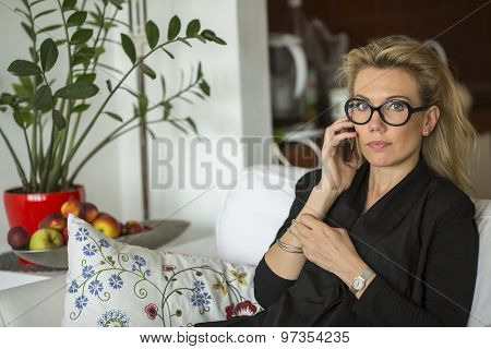 Attractive blond woman talking on phone sitting on a sofa.