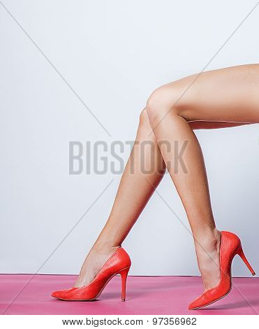 Beautiful female legs with red heels