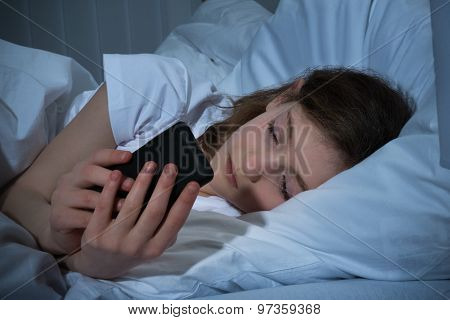 Girl With Mobile Phone On Bed