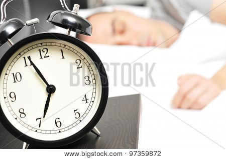 closeup of an alarm clock at 6.55 in the morning on the night table and a young caucasian man sleeping in bed