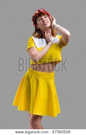 Woman in yellow dress with red wreath isolated on gray