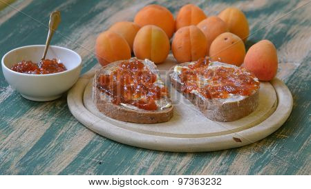 Apricot jam spreaded on bread with apricots on background