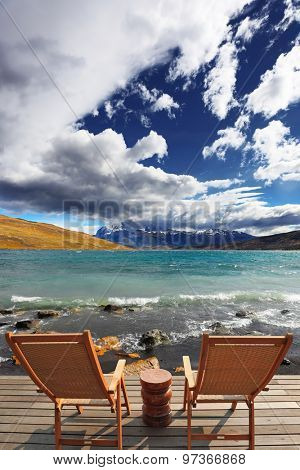 Two folding wooden chairs and a small bedside table on the boardwalk.The comfortable place to enjoy the beauty of the lake and clouds in Patagonia