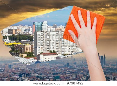 Hand Deletes Smog In City By Orange Cloth