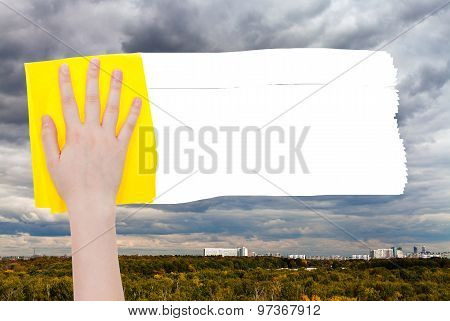 Hand Deletes Rainy Clouds Over Town By Yellow Rag